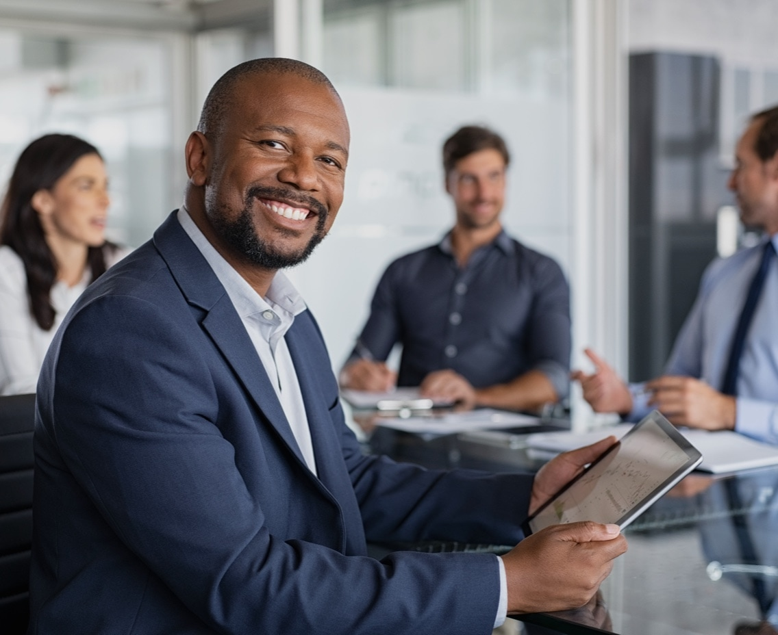 Smiling business man holding iPad sitting in an office